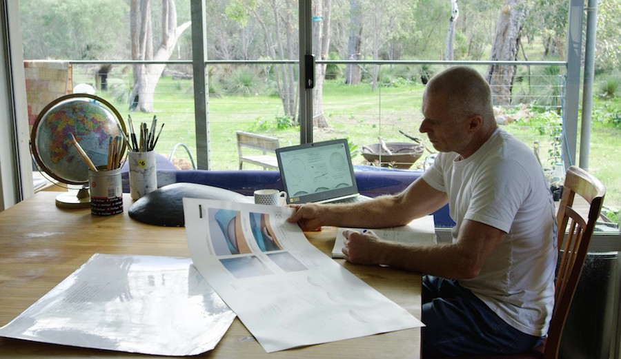 Troy at desk with drawings